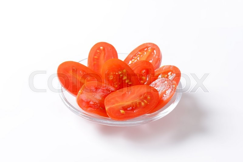 Stock image of 'Halved oblong red tomatoes on glass plate'