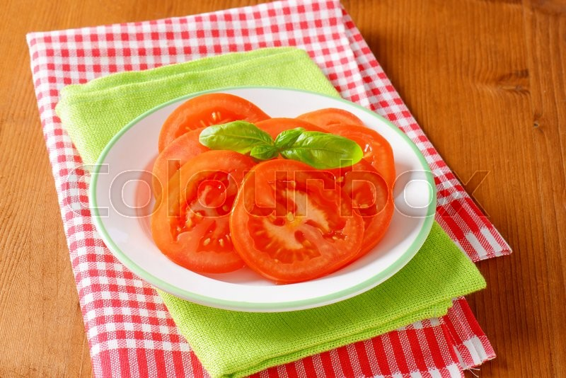 Stock image of 'sliced tomato with basil on white plate'