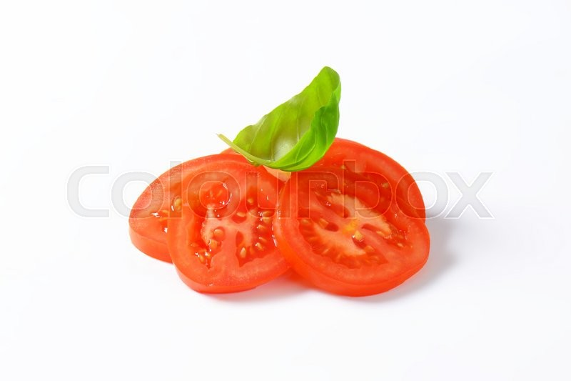 Stock image of 'sliced tomato and basil leaves on white background'