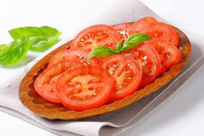 Stock image of 'sliced tomato in wooden bowl'