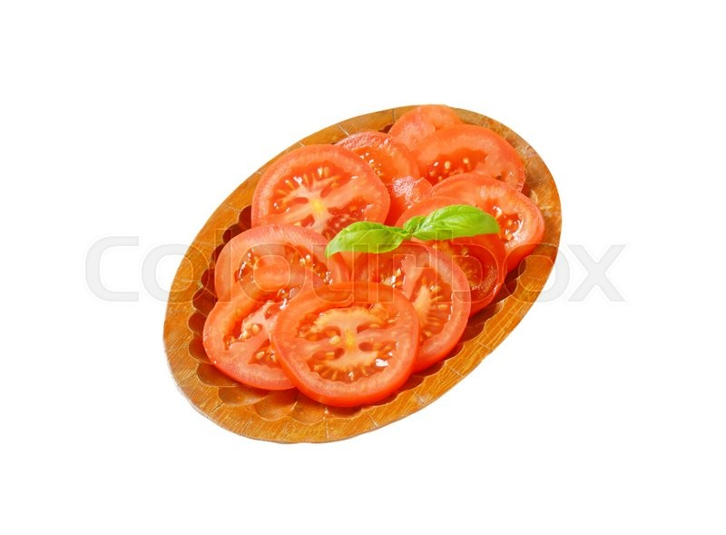Stock image of 'Sliced tomato on wooden plate'