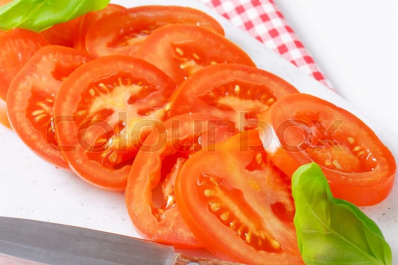 Stock image of 'sliced tomato and kitchen knife on plastic cutting board'