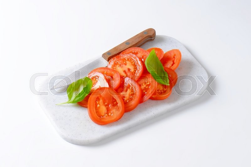 Stock image of 'tomato slices and kitchen knife on plastic cutting board'