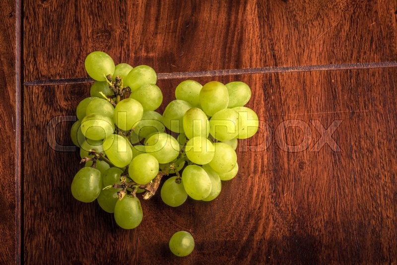 Stock image of 'Pile of green grapes on a dark wooden table'