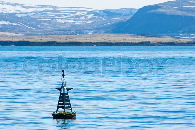 Stock image of 'Buoy silhouette in the blue ocean with mountains in the background'