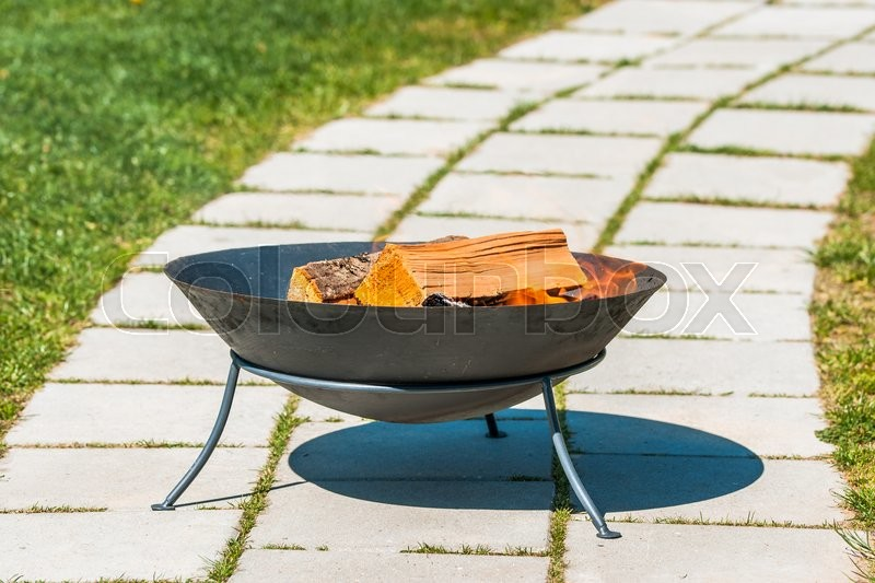 Stock image of 'Outdoor fireplace with wood in a garden'