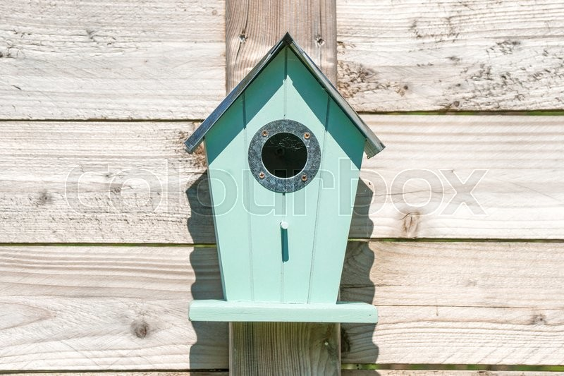 Stock image of 'Blue birdhouse on a wooden fence in a garden'