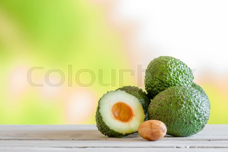 Stock image of 'Pile of green avocado on a wooden table'