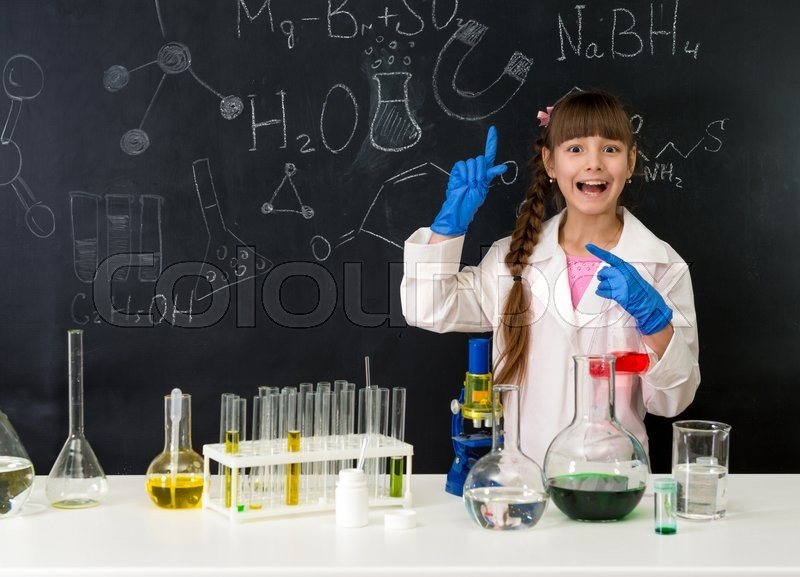 Stock image of 'schoolgirl in chemistry lab in white gown pointing at formula on blackboard near table with reagents'