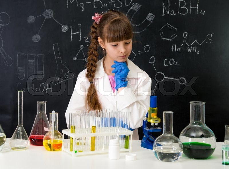 Stock image of 'little smarl girl in white gown in chemistry lab doing an experiment'