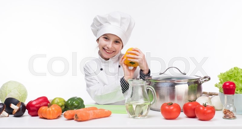 Stock image of 'little girl-cook by table with vegetables in white uniform'