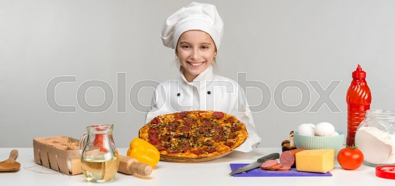 Stock image of 'little girl-cook with pizza in hands by kitchen table with ingredients'