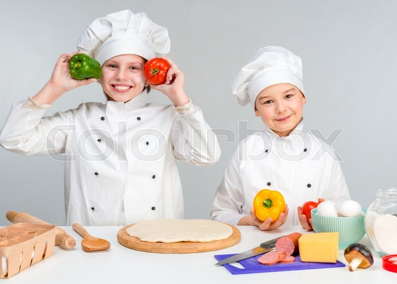 Stock image of 'little boy and girl in white uniform of chef by the table prepare pizza'