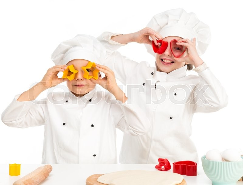 Stock image of 'children-cooks in white uniform playing forms for dought cutting by kitchen table'