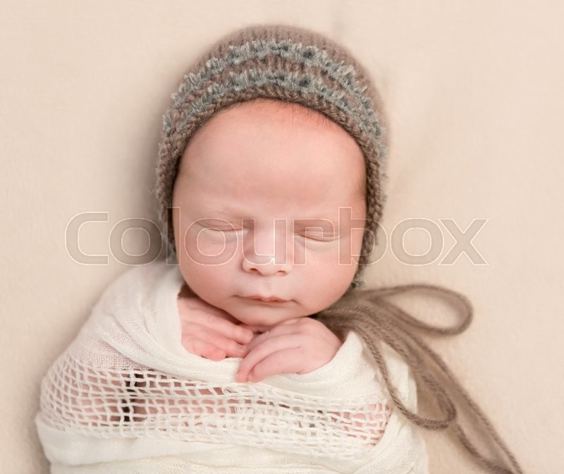 Stock image of 'lovely face of sleepy swaddled newborn baby in knitted hat'