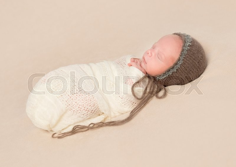 Stock image of 'beautiful sleepy swaddled newborn baby in knitted hat '