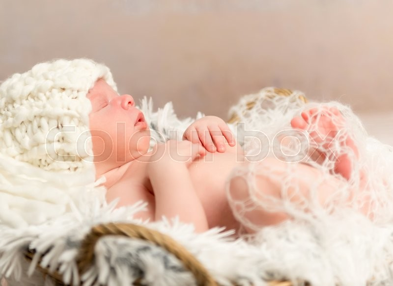Stock image of 'lovely face of newborn baby in knitted white hat lying on fur'
