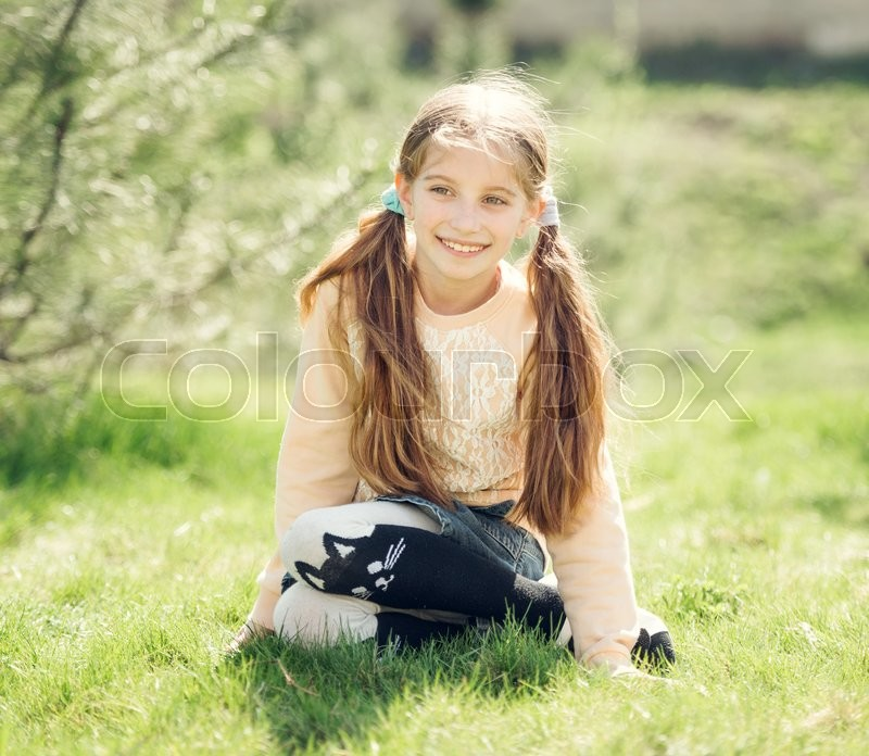 Stock image of 'cute smiling little girl sitting on the grass in park looking away'