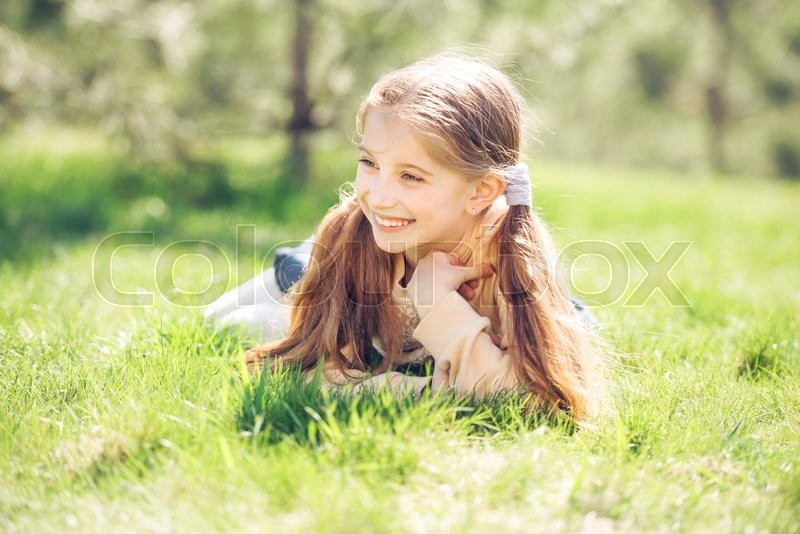 Stock image of 'cute smiling little girl lying on the grass in park looking away'