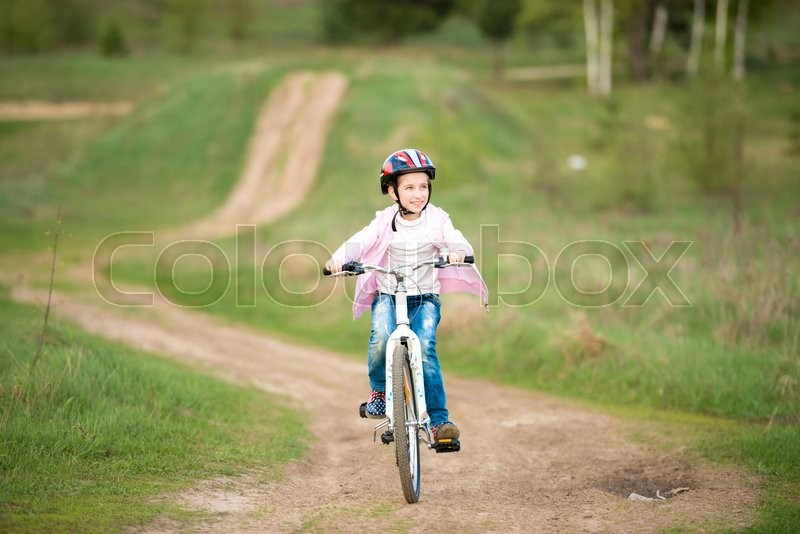Stock image of 'smiling little girl riding a bike in helmet '