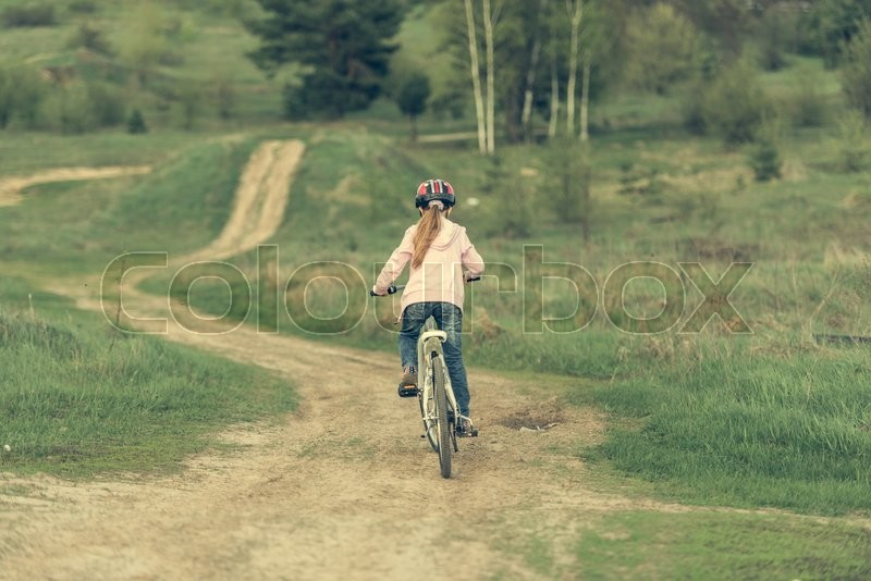 Stock image of 'smiling little girl riding a bike in helmet. back view'