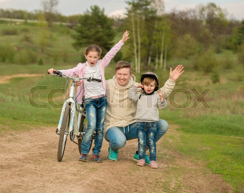 Stock image of 'father with two little daughters walking with bike in a countryside'