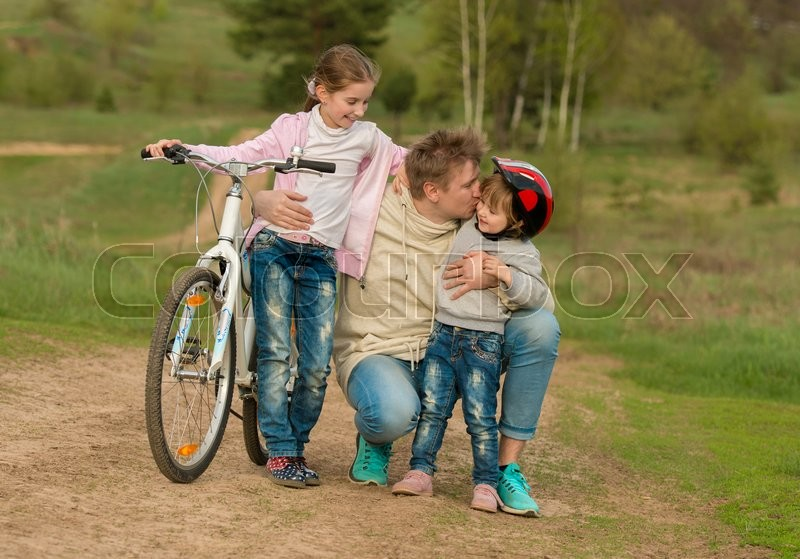 Stock image of 'two little girls with father embracing and kissing outside with bicycle'