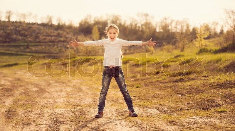 Stock image of 'cute little girl standing with hands to sides on a road in countryside'