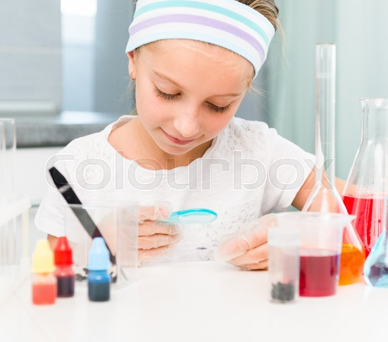 Stock image of 'cute little girl with flasks for chemistry'