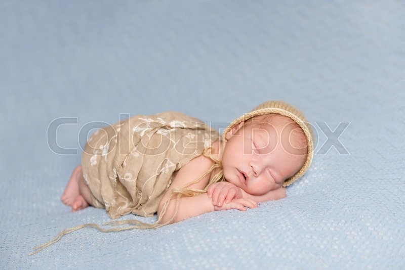 Stock image of 'sleeping newborn baby with lovely cheeks in hat covered with a blanket '