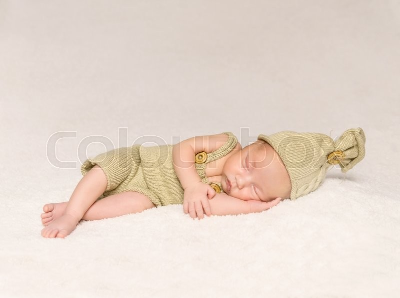 Stock image of 'sweet newborn baby sleeping in costume and hat with teddy-bear'