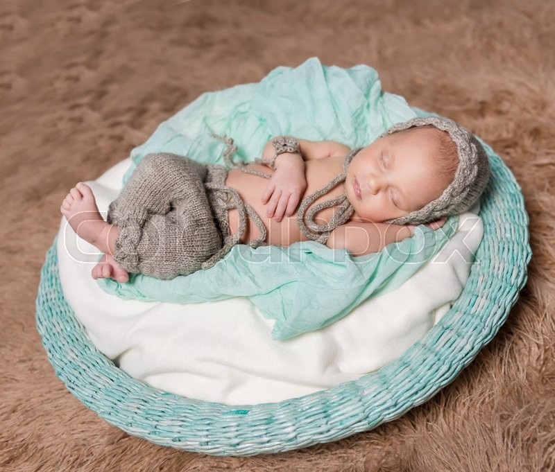 Stock image of 'newborn baby sleeping in round basket with knitted hat and toy'