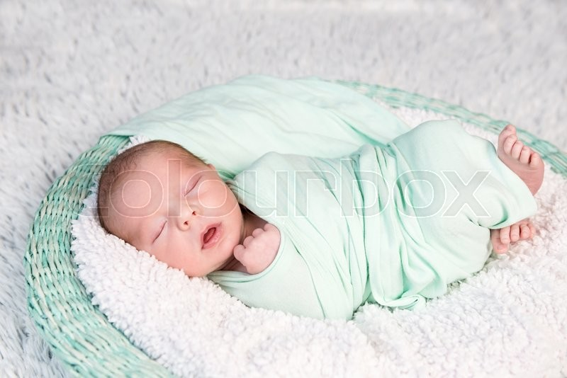 Stock image of 'sweet wrapped in a nappy newborn baby sleeping on a soft blanket'