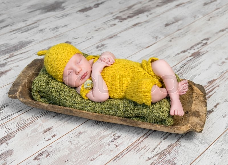 Stock image of 'newborn baby in yellow costume sleeping on wooden cot top view'