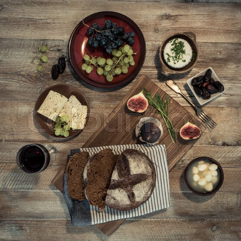 Stock image of 'bread with cheeses and grapes and wineglass on wooden background'
