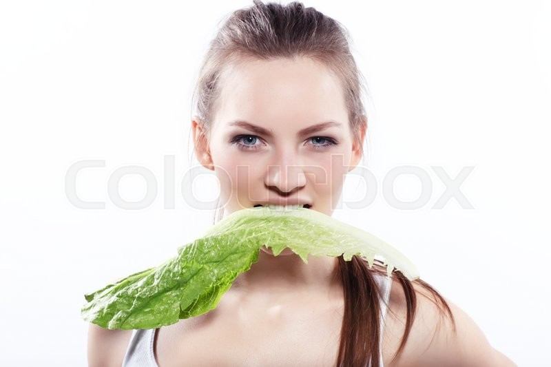 Stock image of 'Attractive woman is biting lettuce on white background '