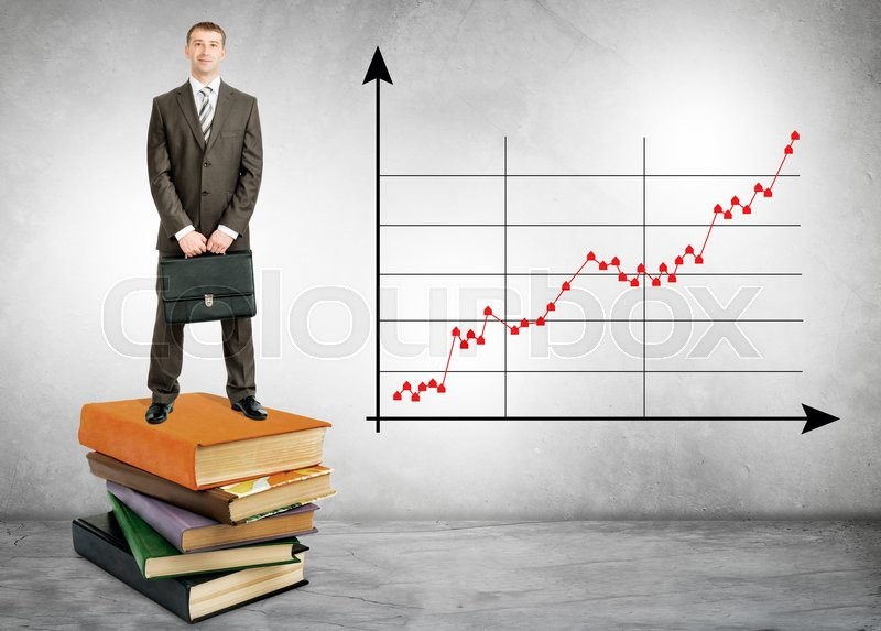 Stock image of 'Businessman standing on books with growth chart on wall'