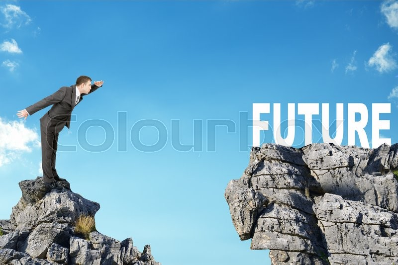 Stock image of 'Young businessman standing on edge of rock mountain and looking at word future'