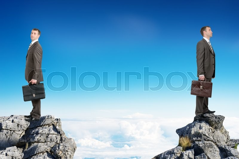 Stock image of 'Young businessmen with suitcases standing on peaks with their backs to each other'