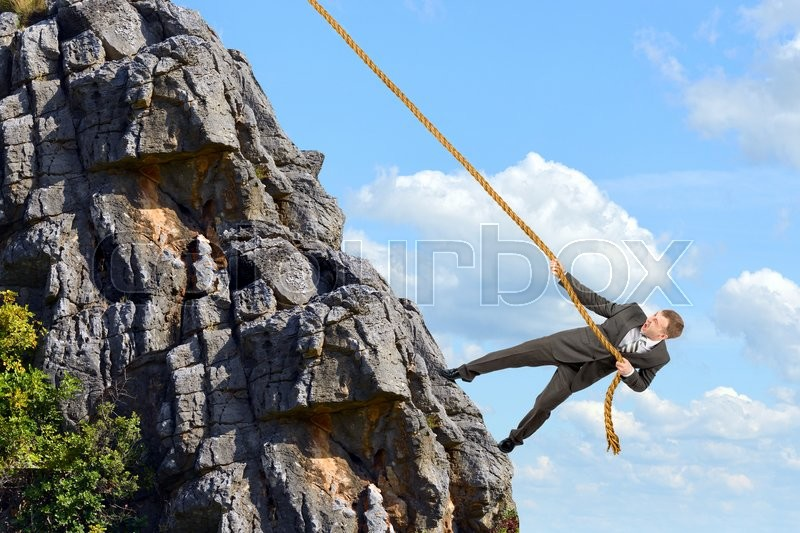 Stock image of 'Business man climbs mountain within help of rope'