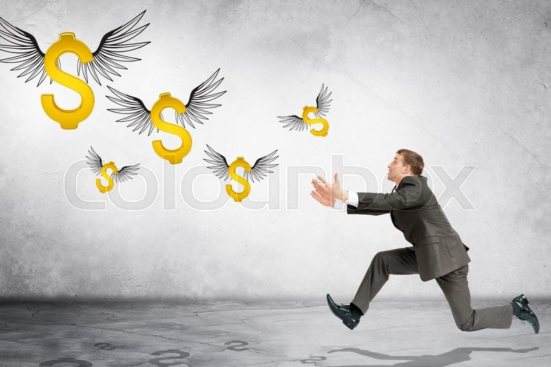Stock image of 'Business man running to catch flying dollar sign on gray background'