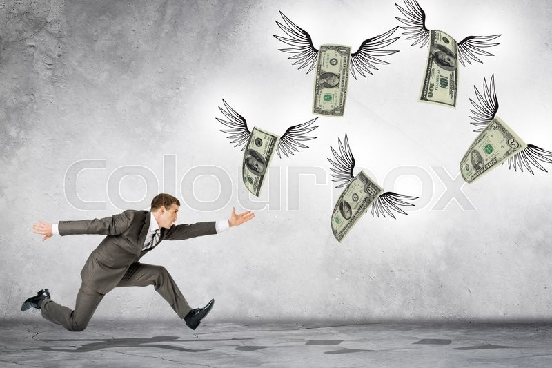 Stock image of 'Business man running to catch flying dollars on gray background'