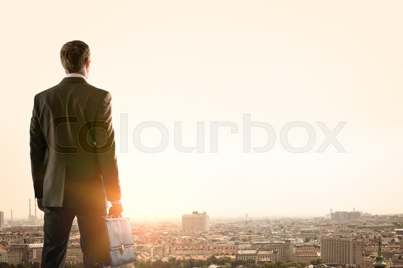 Stock image of 'Businessman standing with back against morning city, panoramic view'