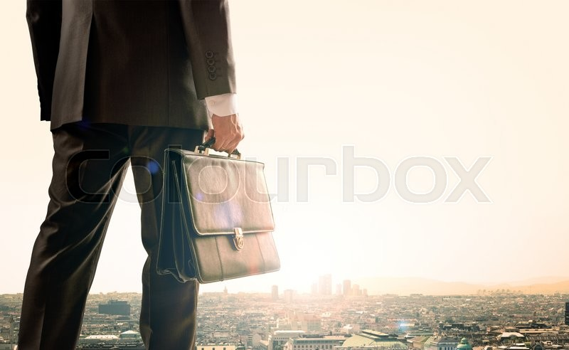 Stock image of 'Businessman with suitcase standing with back against morning city, panoramic view'