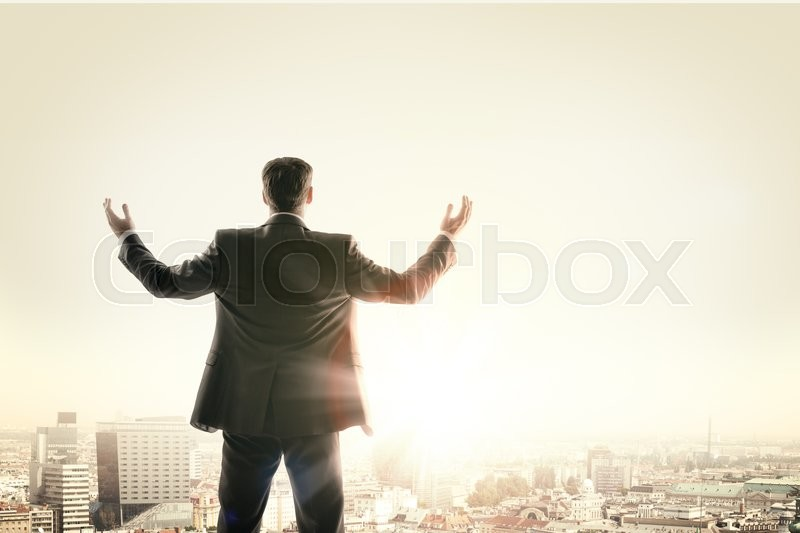 Stock image of 'Happy businessman looks sunrise in city, concept for business'