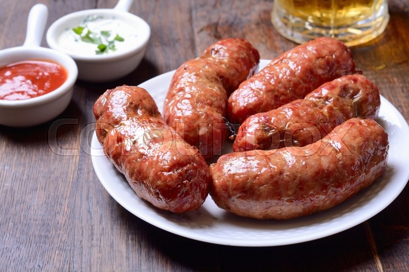 Stock image of 'Baked meat sausage on wooden background'