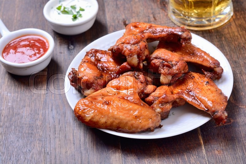 Stock image of 'Baked meat wings on wooden background'