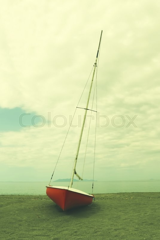 Stock image of 'This photo of red boat on coastline'