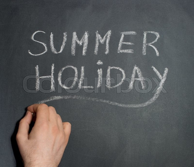 Stock image of 'Man's hand writing Summer Holiday text on blackboard.'