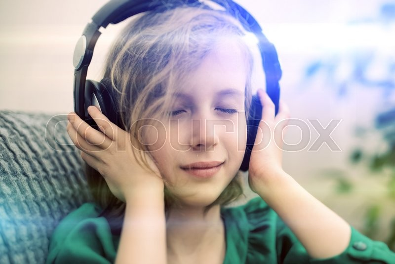 Stock image of 'Little girl listening to the music in headphones.'